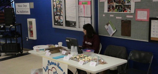 Senior Dory Psomas watches over a bake sale being held in the hallway outside the library. Photo: Derek Smith